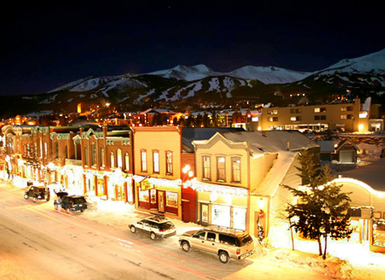 Year-round Activities Breckenridge, winter night scene with shops lit up and Breckenridge resort ski runs in the background