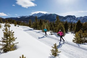 Activities Nordic Skiing, 2 women on groomed nordic trails with trees and mountains