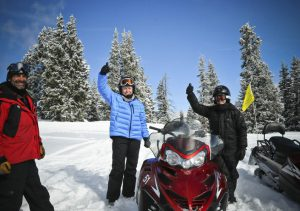 Activities Snowmobiling, 3 adults with 2 snowmobiles in a winter scene