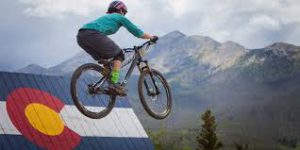 Alpine Villa Activities Mountain Biking, mountain biker on a jump in front of wooden Colorado state flag with mountain backdrop
