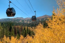 Alpine Villa Activities Fall Gondola rides, 2 gondolas over yellow aspen trees with Breckenridge ski resort backdrop