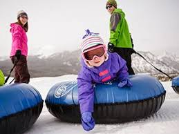 Activities Snow Tubing, 2 adults, 1 child in blue tubes with mountains in the background