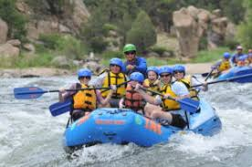 Activities Whitewater Rafting, 6 rafters with guide on the river with a blue raft