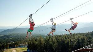 Alpine Villa Activities Zipline, 3 people suspended on the zipline above the Breckenridge ski resort